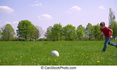 Boy hit the ball on green meadow, slow motion