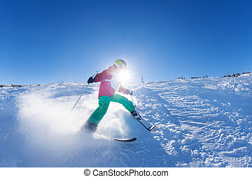 Boy hitting down a slope on ski race at sunny day