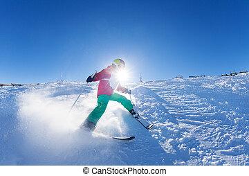 Boy hitting down a slope on ski race at sunny day