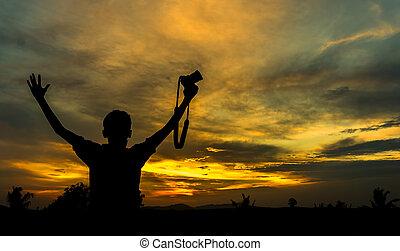 Boy hold camera silhoutte with orange skies