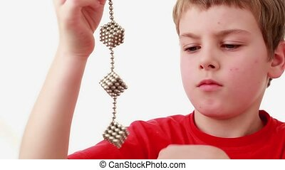 Boy hold chain compound of magnet spheres cubic structures,...