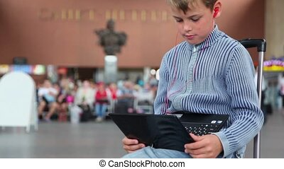 boy hold netbook when sits on travelling bag at train station