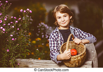 boy holding a basket of fruit in the garden