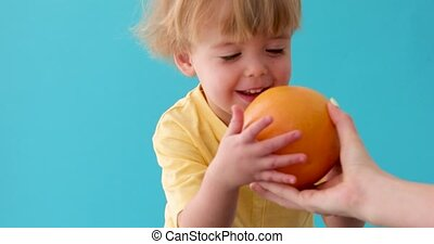 Boy holding a grapefruit. Healthy food - Adult gives a kid a...