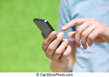 boy holding a phone and a touch screen for finger against a...