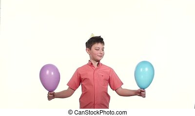 boy holding a two balloons and releasing them into the air,...