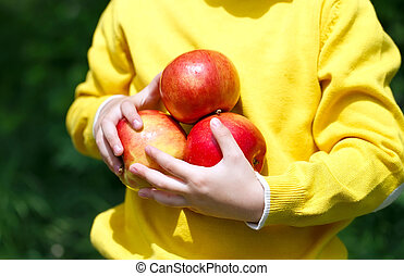 boy holding apples in the open air in the forest.