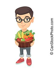 Boy holding basket with fruit and vegetables.