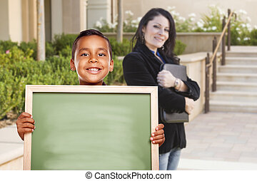 Boy Holding Blank Chalk Board on Campus with Teacher Behind