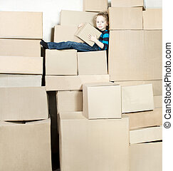 Boy holding box is sitting on the top of heap of carton packed boxes