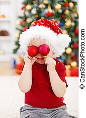 Boy holding Christmas decoration in front of eyes