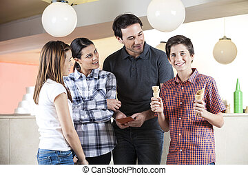 Boy Holding Cones By Family In Ice Cream Parlor
