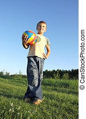 Boy holding football looking to camera faraway
