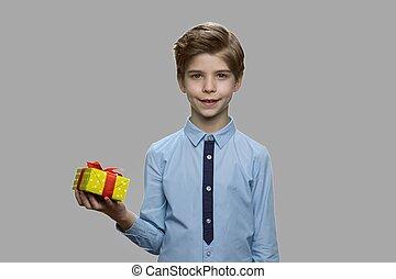 Boy holding gift box on gray background.
