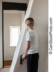 Boy Holding Gun Waiting Someone Behind the Wall