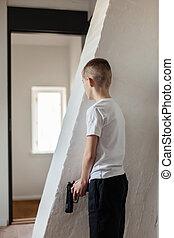 Boy Holding Gun Waiting Someone Behind the Wall