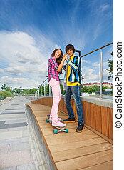 Boy holding hands of girl on skateboard