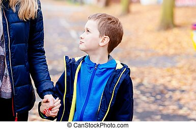 Boy holding his mother hand