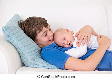 Boy holding his newborn baby brother