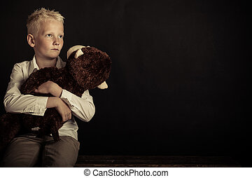 Boy holding large plush toy over black background - Single ...