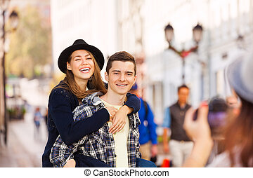Boy holding laughing woman and girl shooting them