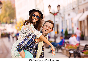 Boy holding laughing young woman on the back