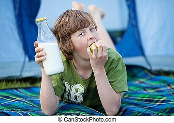 Boy Holding Milk Bottle And Eating Apple While Lying On Blanket