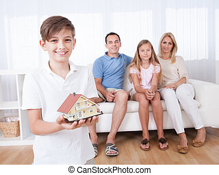 Boy Holding Miniature Model Of House