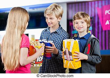 Boy Holding Popcorn While Siblings Talking At Cinema