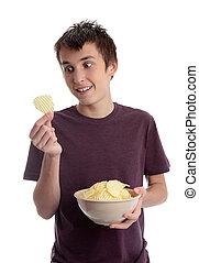 Boy holding potato crisp and smiling