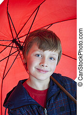 boy holding red umbrella