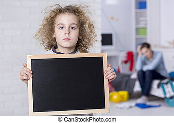 Boy holding small blackboard