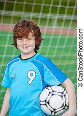 Boy Holding Soccer Ball Against Net
