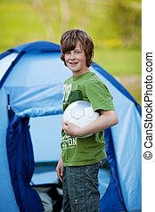 Boy Holding Soccer Ball Against Tent