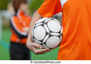 Cropped image of boy holding soccer ball on field