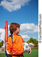 Boy Holding Soccer Ball While Looking Away At Corner Flag