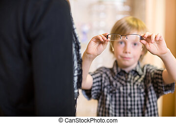 Boy Holding Spectacles With Mother In Foreground At Shop