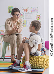 Boy holding teddy bear during therapy