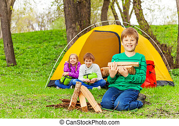 Boy holding the wood for bonfire with other kids