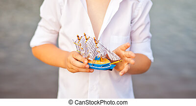 Boy holding toy boat, model of the ship