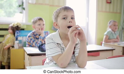 Boy holds a pencil in his mouth, thinking with a pencil in his mouth