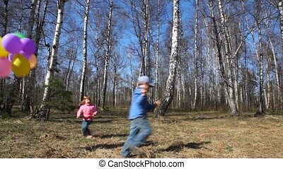 boy holds balloons and girl runs around - boy holds bunch of...