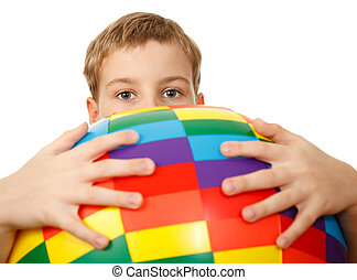 Boy holds in front of himself big, multi-coloured, inflatable ball, looking out from behind it. Looks in camera.