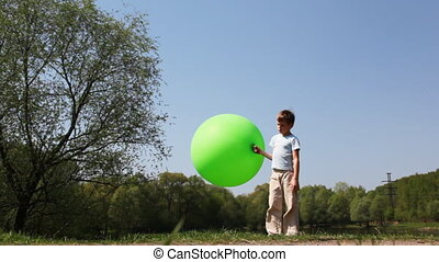 Boy holds inflatable ball, then carefully goes barefoot on...