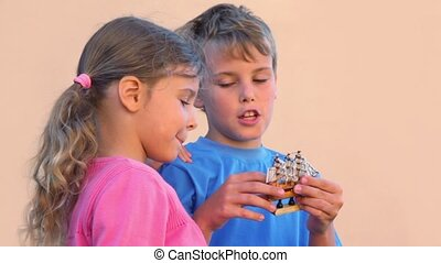 boy holds model of tall ship and talks with sister