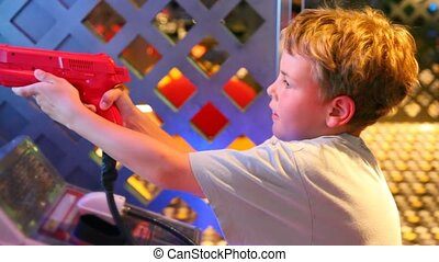 boy holds red gun of video game and shoots from it