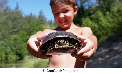 Boy Holds Turtle in Arms and Smiles Viciously on Background of River with Green Vegetation. Tortoise funny moves head in shell. Close-up. Summer day. European pond turtle Emys orbicularis. Slow Motion