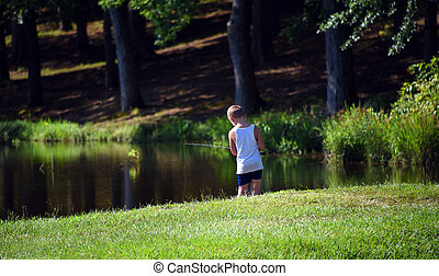 Boy Hopes for a Fish - Young boy stands on the shore of ...
