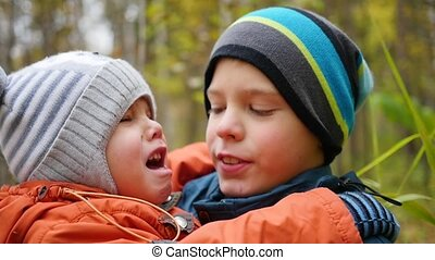 Boy hugging crying younger brother and holding him in my...