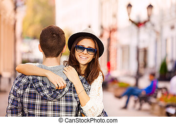 Boy hugging young woman view from the back